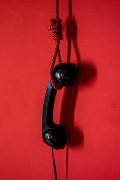 black telephone handset suspended by a red rope noose