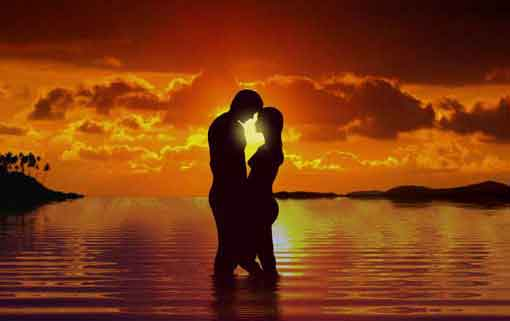 photograph of a silhouetted couple embracing on the beach