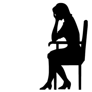 silhouette of woman in chair with head in hands
